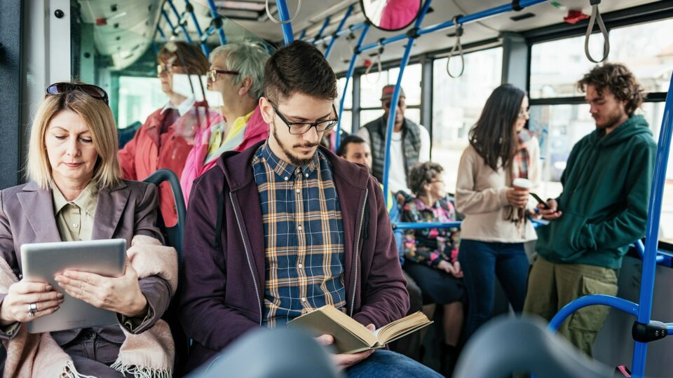 a man in glasses reading a book and a woman on the right side watching on the digital screen over the background of people in the bus