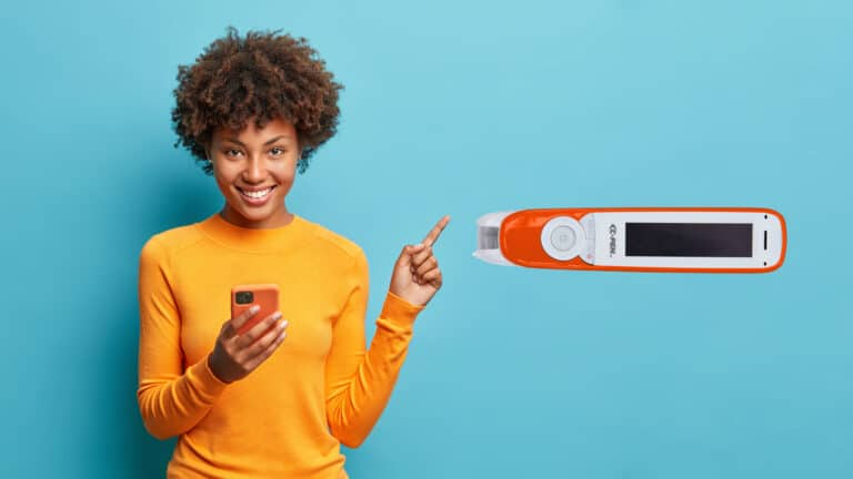A smiling woman holding a mobile and pointing to C-Pen ExamReader over blue background